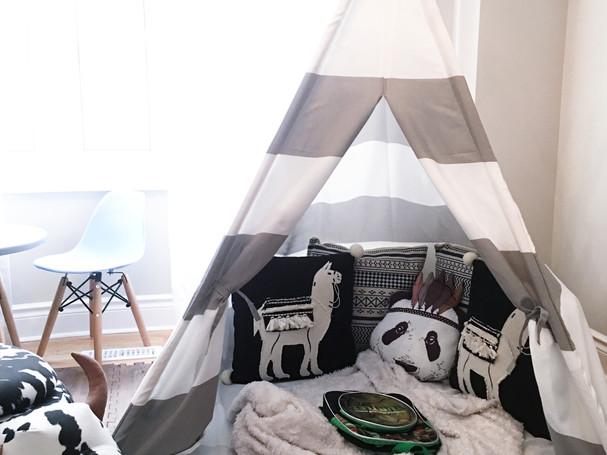 kids playroom with teepee, buffalo storage ottoman, play table and throw pillows