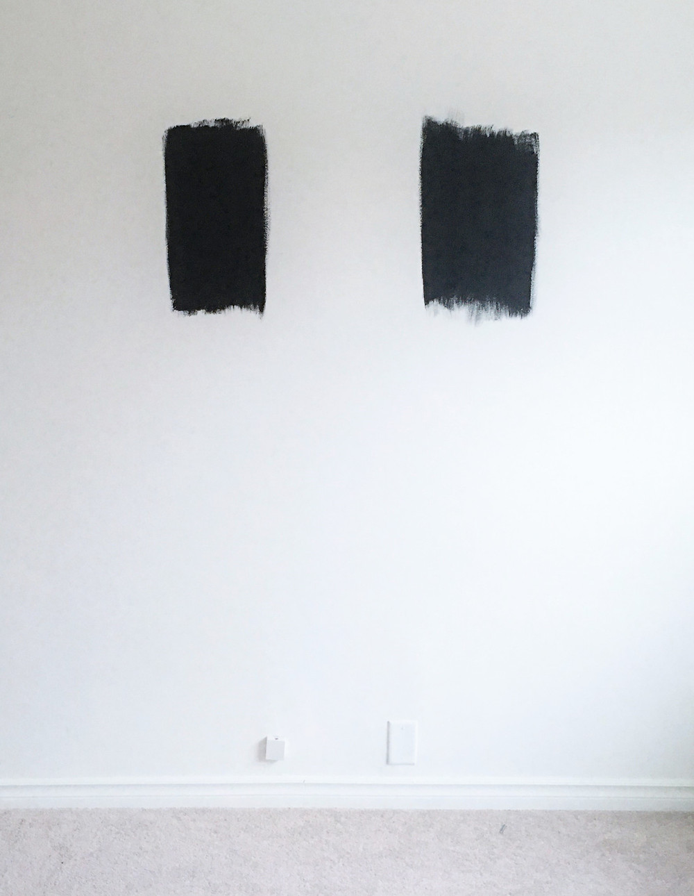 Two Black paint swatches on a bedroom wall