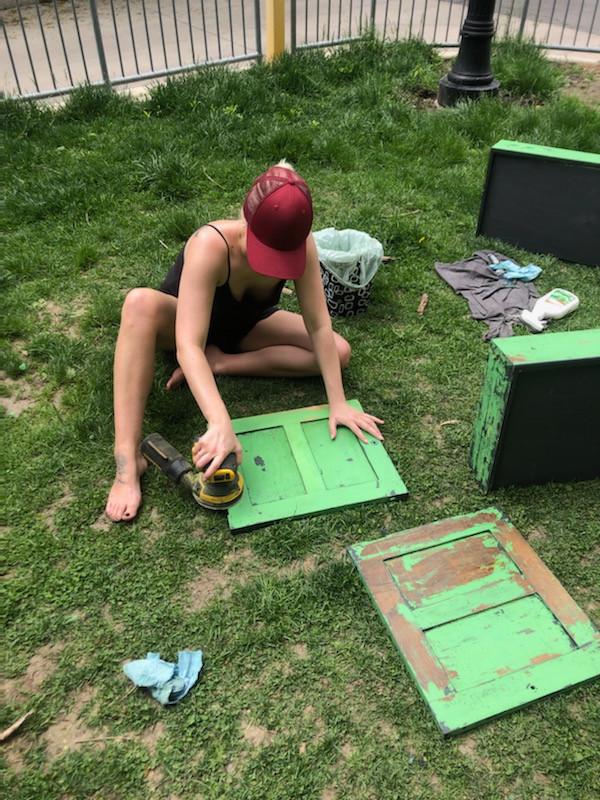 interior designer sanding a navy piece of furniture to repaint