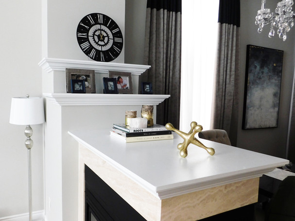 new york style clock on mantel with book stack, rustic wood candles and crystal tea light holder