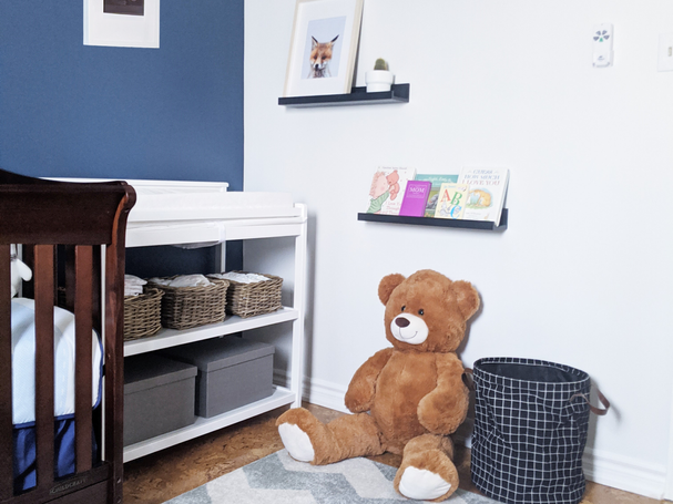 boys nursery with bue wall, oversized teddy bear, black laundry hamper and picture ledges with books and artwork