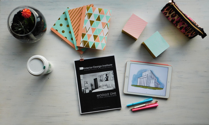 cute desk flat lay with interior design textbook