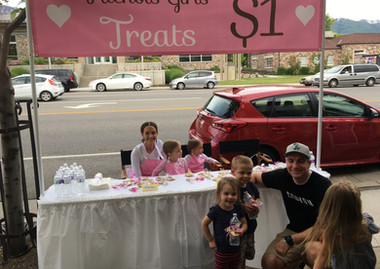 The girls selling cookies at their booth during our town's Main Street summer festival--all in an attempt to save some money to buy a horse!