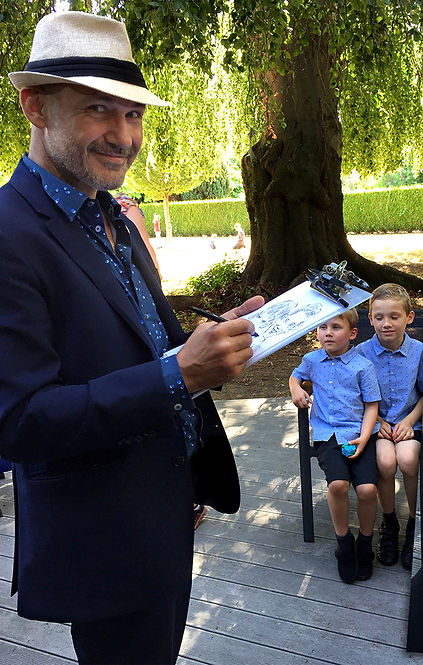 Two boys get their caricature sketched by London party entertainer Alfie Deliss