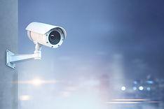 Modern CCTV camera on a wall. A blurred