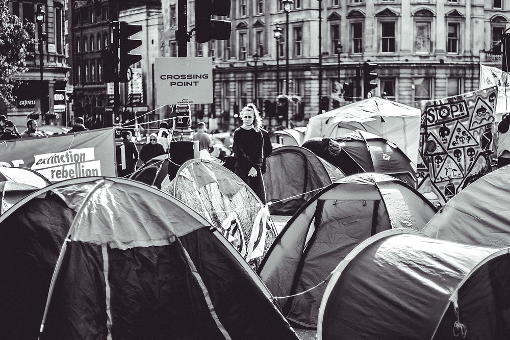 A woman standing among tents at a protest. black and white image