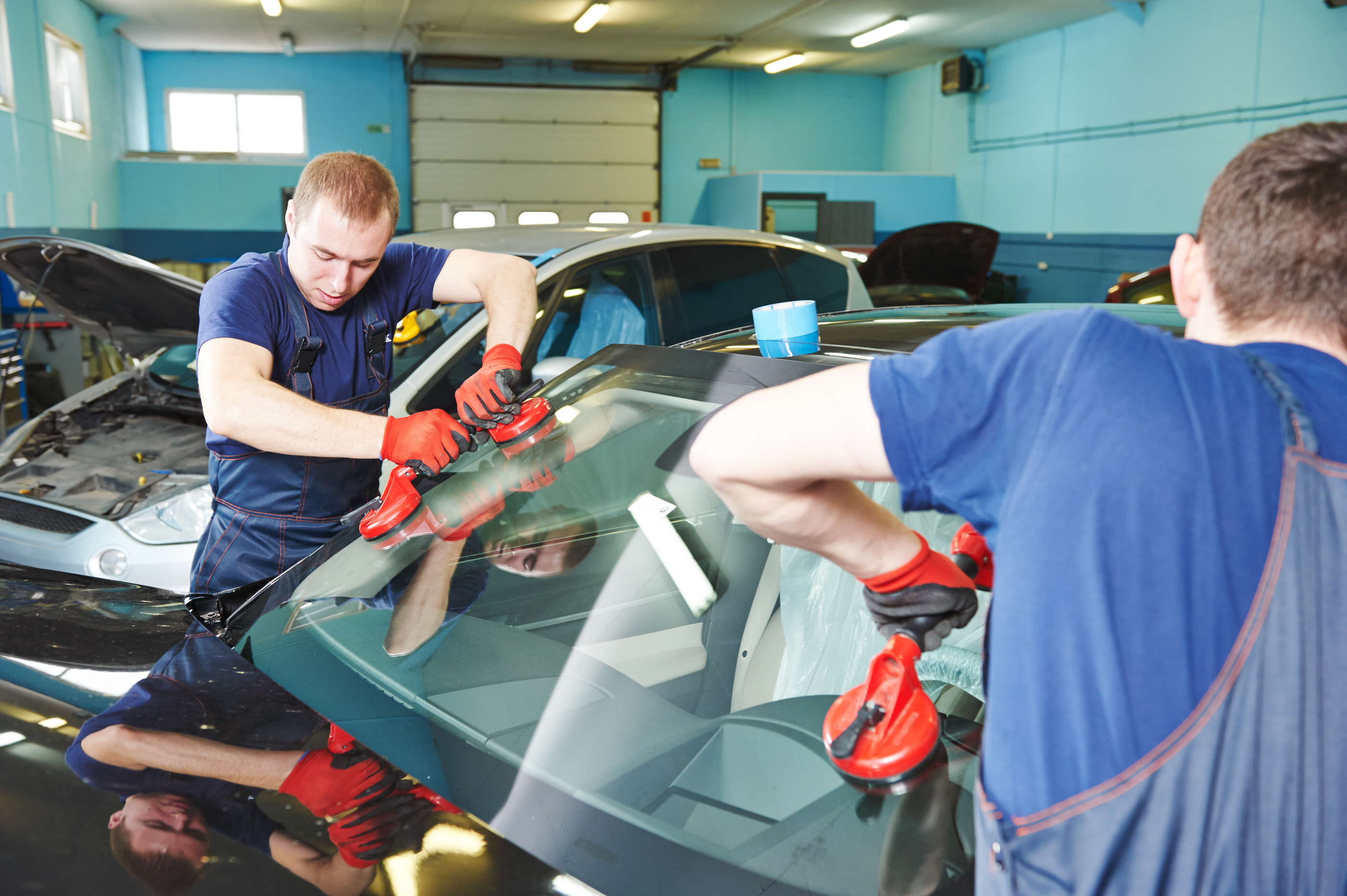 Automobile glazier adding glue on windscreen or windshield of a car in auto service station garage b