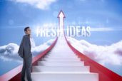The word fresh ideas and smiling businessman standing against red steps arrow pointing up against sky