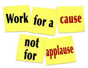 The saying Work for a Cause Not for Applause on yellow sticky notes telling you that it is better to strive for a noble mission or goal than to seek recognition or appreciation
