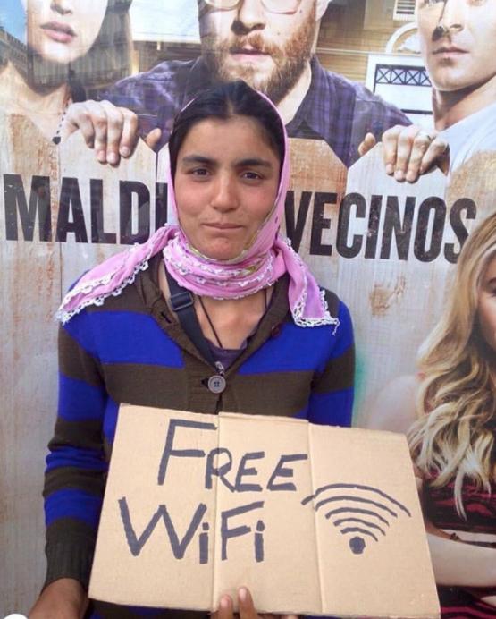 Romani lady holding cardboard Free Wifi sign