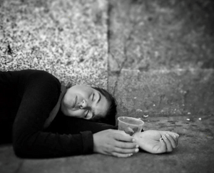 A Romani girl sleeping on a Madrid pavement with plastic cup in hand