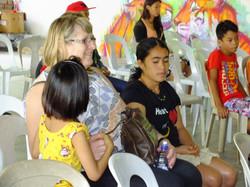 volunteer enjoying children performance for them