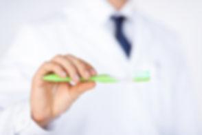 stockfresh_3232379_dentist-or-stomatologist-holding-toothbrush_sizeM.jpg