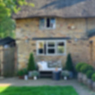 Cotswolds Cottage exterior bench sunny day planters bushes