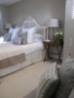 London Townhouse master bedroom ornate headboard grey tones throw pillows