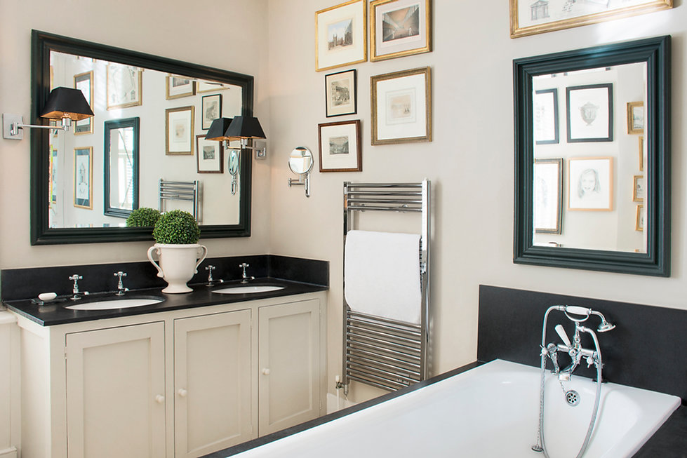 London Townhouse bathroom soaking bath tub white and black gold frames artwork double sink mirrors