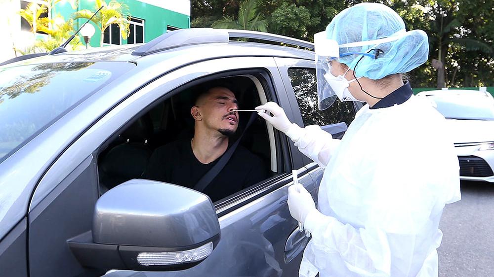 Atleta dentro de um carro, fazendo exame de covid PCR