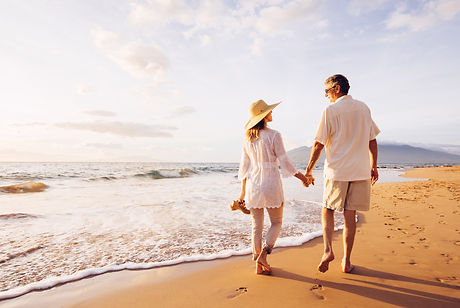 Happy Romantic Middle Aged Couple Enjoying Beautiful Sunset Walk on the Beach. Travel Vaca