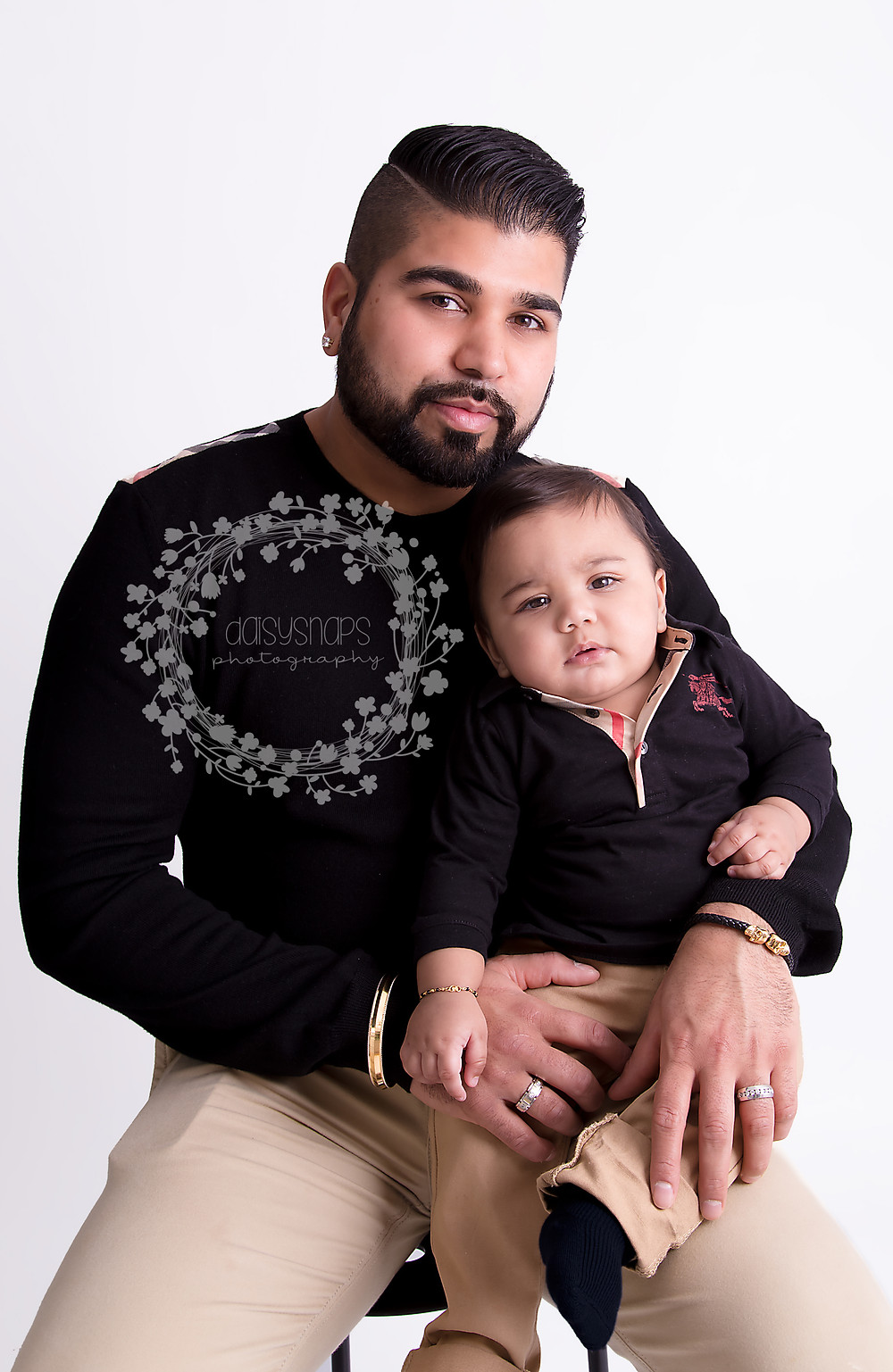 father and son family portrait with baby sitting on dad's lap looking at the photographer