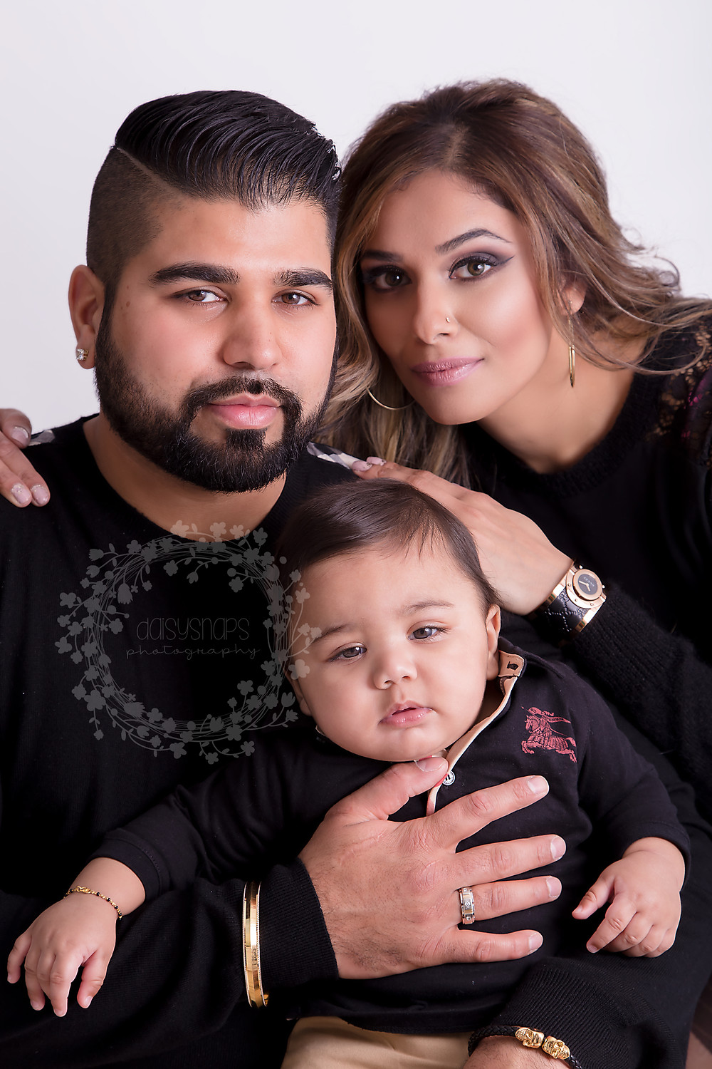family phot session with baby boy sitting on dads lap and mother hugging family