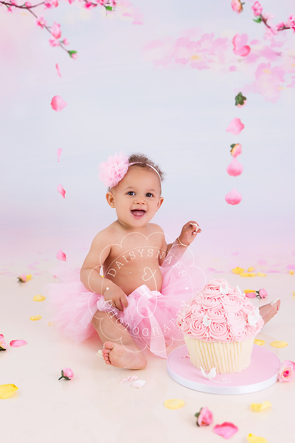 a little girl sitting by her giant cupcake iced with pink buttercream smiling as she takes her first bite to celebrate her first birthday cake smash in kent