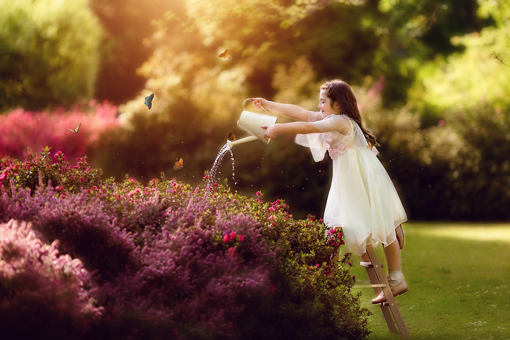 whimsical photography with girl watering the flowerbed