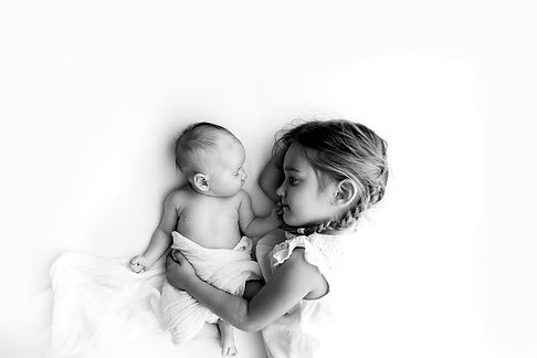 big sister holding her newborn baby sister, black and white timeless photography
