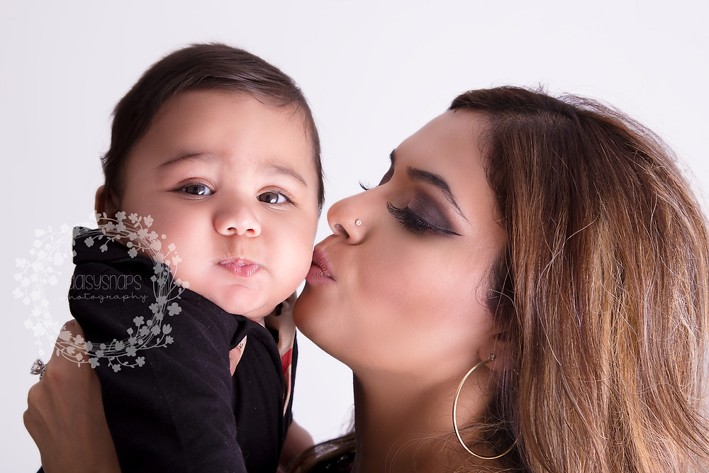mother and baby photo session went very well with mother kissing baby on his cheek makes a great photo session