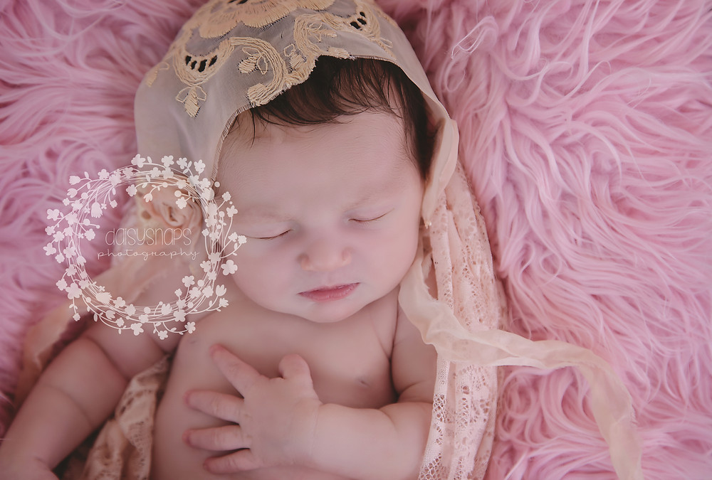 tiny little newborn sleeping beauty in a basket all wrapped up in lace