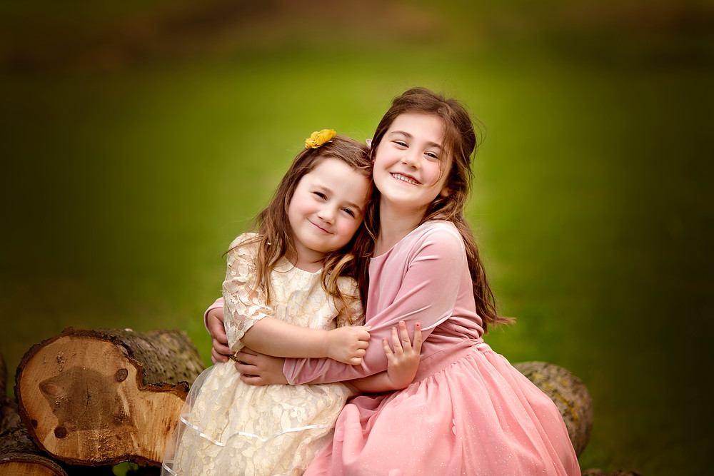 sisters sitting on wooden logs hugging, family photographer kent, family photographers, hall place, outdoor photo sessions, woodland photo sessions, photographers in kent, family photo shoots, location photo shoots