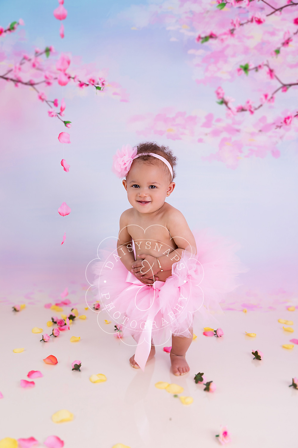 a little girl dancing to the sound of mum and dad singing, the scene is set with a cherry blossom backdrop and roses and petals on the floor for her first birthday photo session