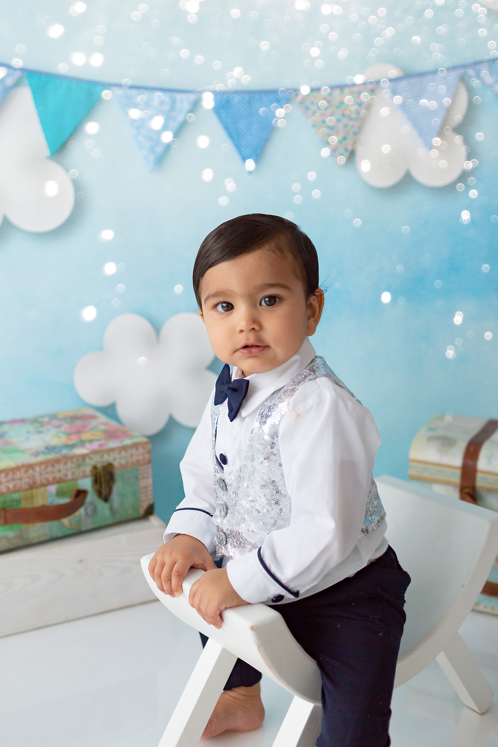 Cake Smash photography, handsome as ever, a little boy turning one sat on his stool wearing a suit and bow tie!