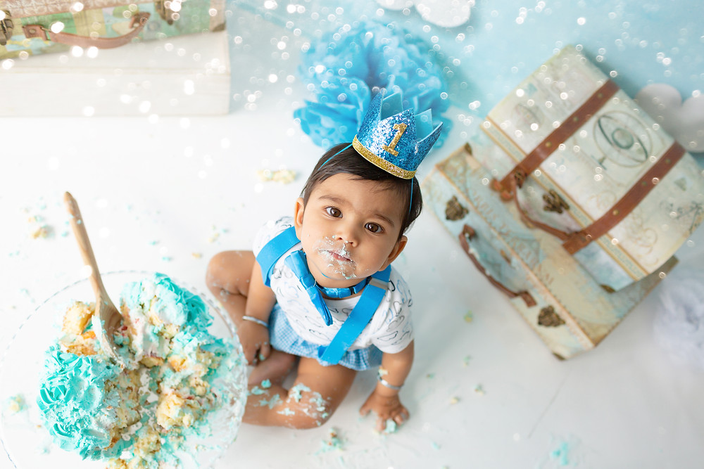 beautiful themed cake smash sessions london, baby boy with cheeks full of buttercream, look at all the mess!