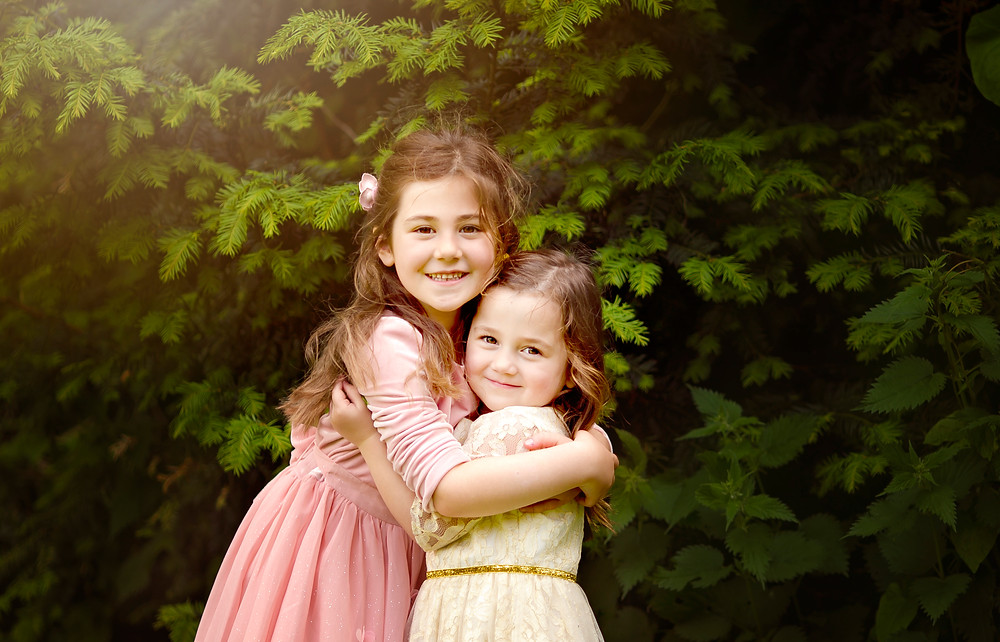 sisters hugging, family photographer kent, family photographers, hall place, outdoor photo sessions, woodland photo sessions, photographers in kent, family photo shoots, location photo shoots