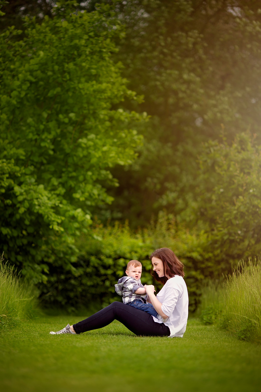 kent family Photographer. mum and baby sitting on green grass in the sunset