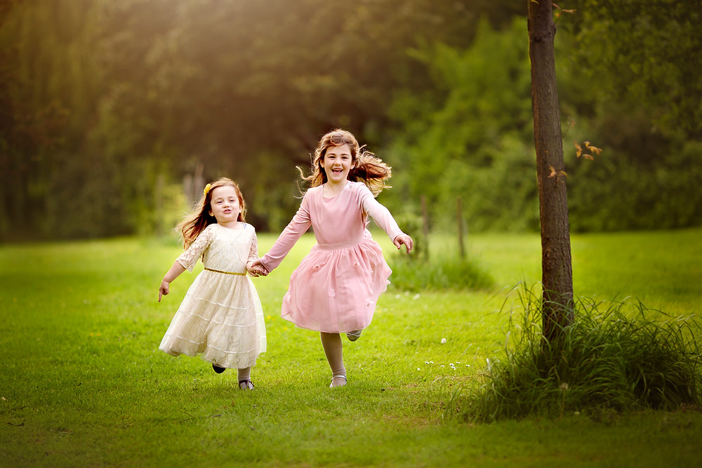 sisters running holding hands, family photographer kent, family photographers, hall place, outdoor photo sessions, woodland photo sessions, photographers in kent, family photo shoots, location photo shoots
