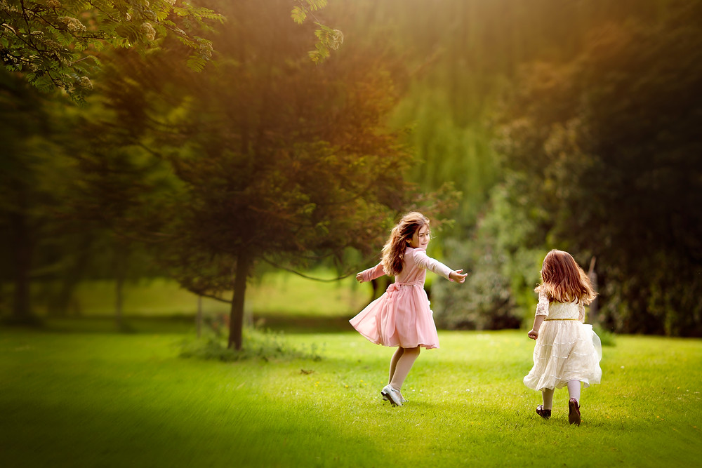 sisters running and playing on the grass,family photographer kent, family photographers, hall place, outdoor photo sessions, woodland photo sessions, photographers in kent, family photo shoots, location photo shoots