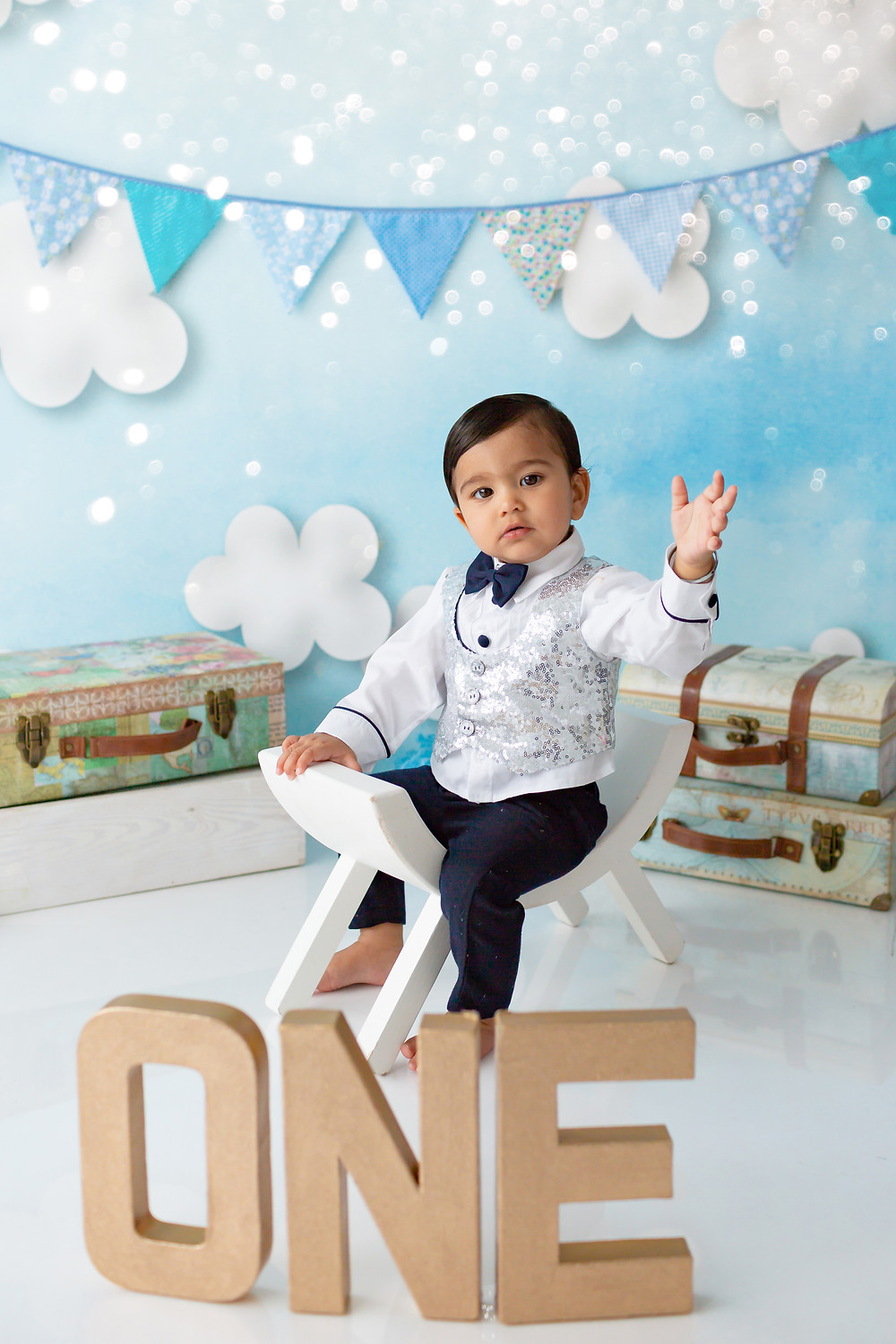 very handsome little boy sitting on his white stool waving at the camera! he is turning one!