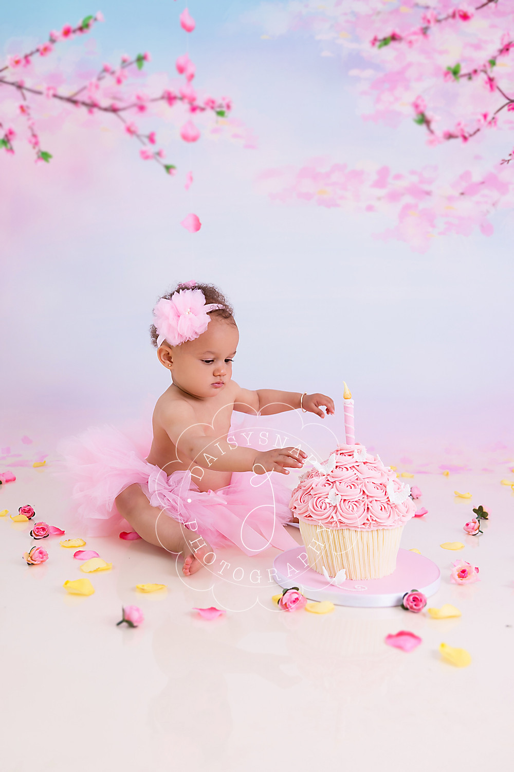 little baby girl dressed in a pink tutu is sitting in front of her giant cupcake surrounded by flowers and a cherry blossom backdrop