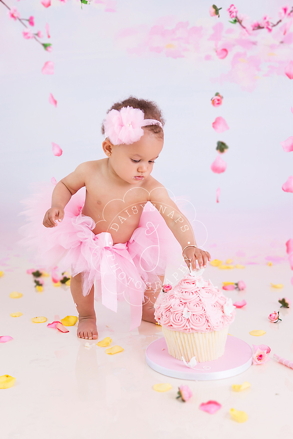 a little baby girl standing in front of her giant cupcake picking off decorations  to eat on her first birthday cake smash photo shoot