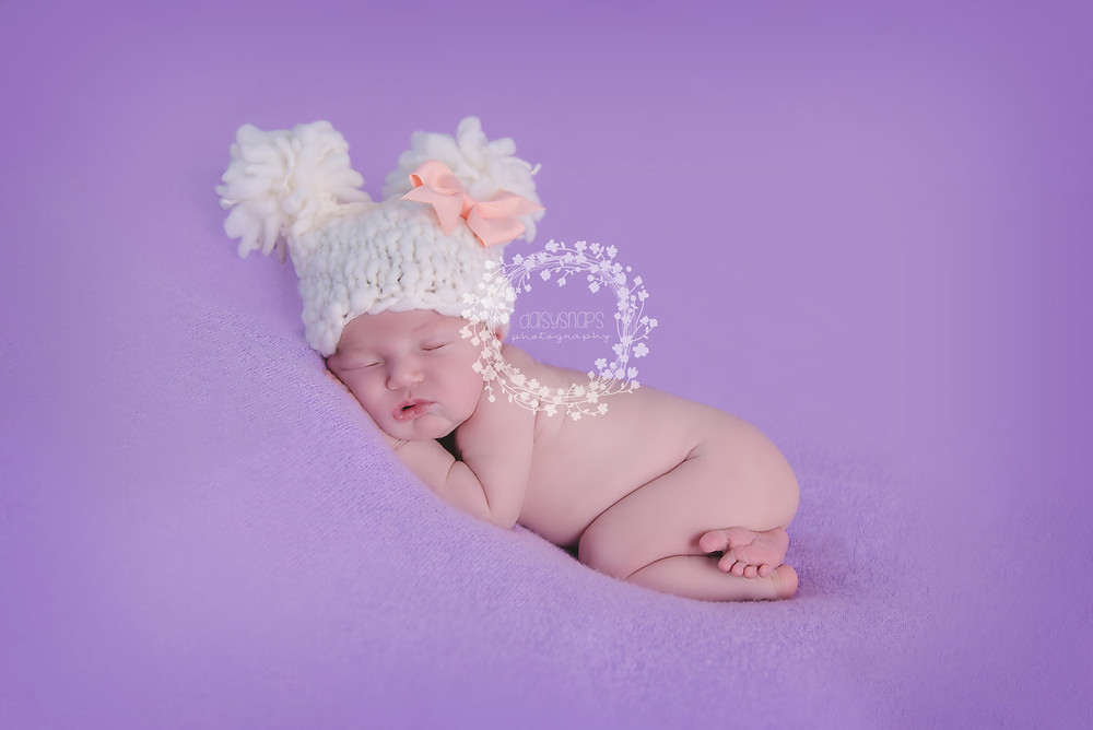 cute little newborn baby girl lying posed on her tummy wearing a knitted hat