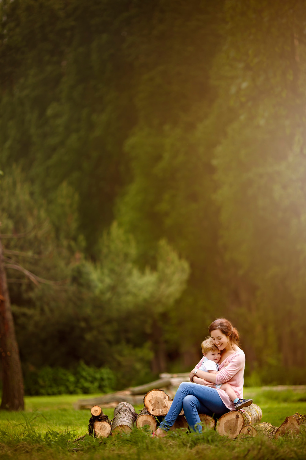 mum and son sitting on logs in the sunset,family photographer kent, family photographers, hall place, outdoor photo sessions, woodland photo sessions, photographers in kent, family photo shoots, location photo shoots