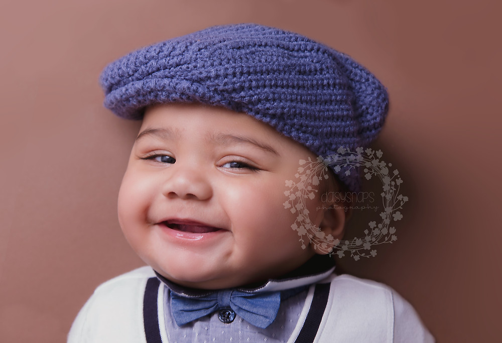 smiling baby boy wearing blue knitted baker boy hat