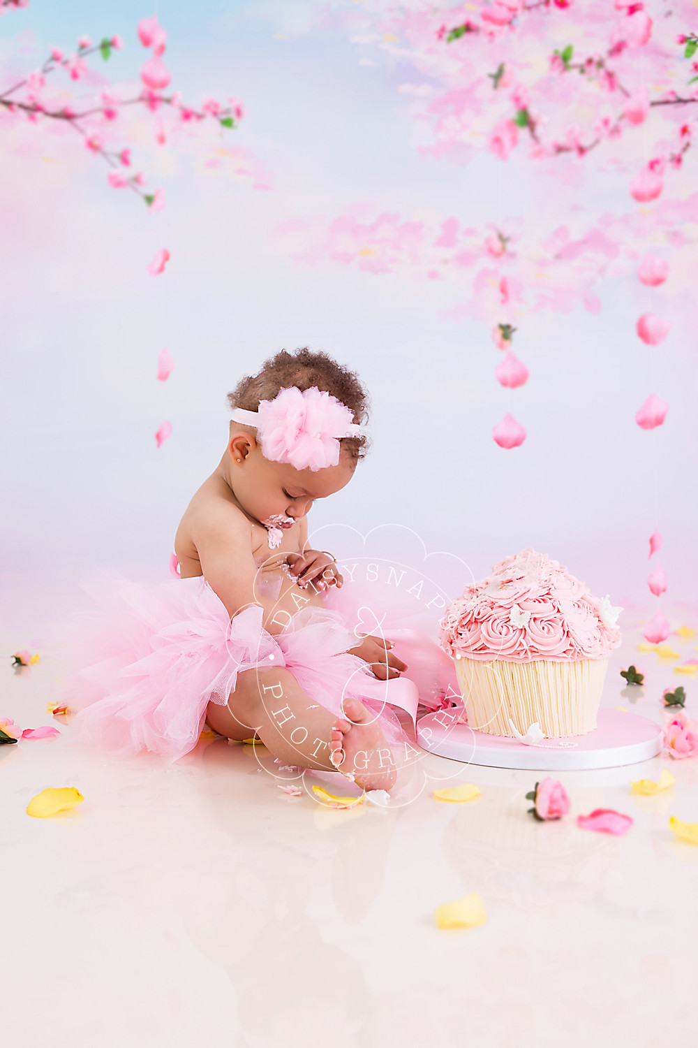a little baby girl celebrating her first birthday cake smash in kent sitting in front of her beautiful iced cake, she has icing on her belly and is looking down to rub it off