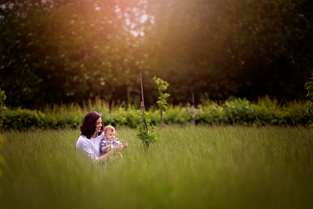 mother and baby sitting in long grass during golden hour. kent family photographers
