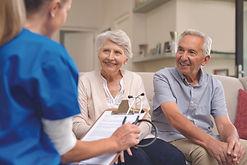 senior-couple-consulting-nurse-125353349
