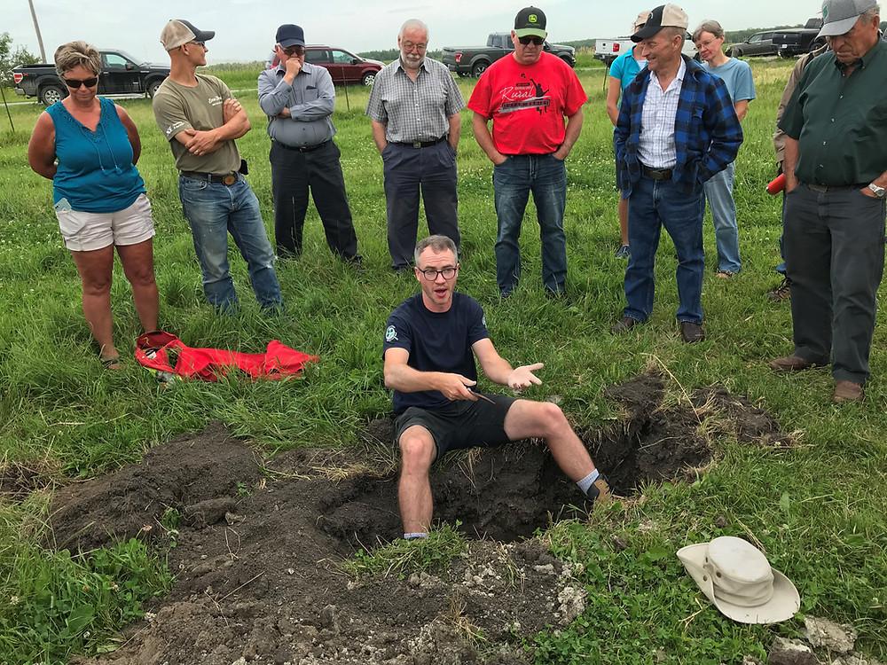 OMAFRA Soil Management Specialist Sebastian Belliard explains the soil pit.