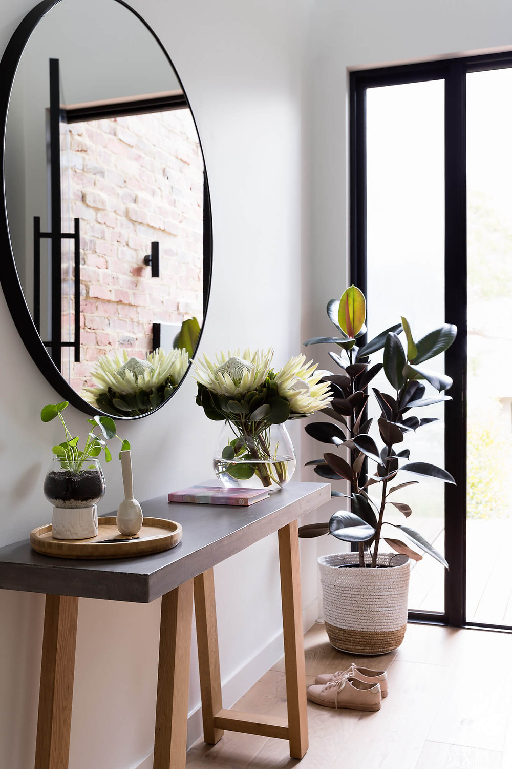 Entry foyer with table, plants and mirror