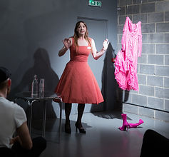 A white person who appears to be male stands in the corner grey room, one wall is made of exposed grey breezeblocks. The person is lit and addressing an audience seated in front of them on chairs. They wear a 1950s style red a-line dress with white spots, black tights and balck high heeled shoes. They have long brown hair and femine makeup. Their arms are raised in an emphatic gesture.