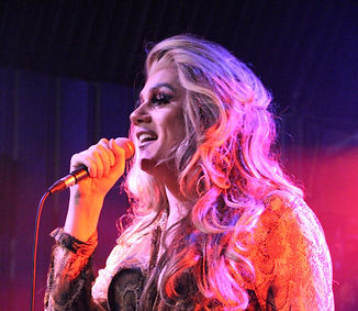 Ophelia, a drag queen sings into a microphone, she is smiling. She wears a snake skin effect shirt. She has long, blond-white hair. She stands on stage, with pink light behind her.